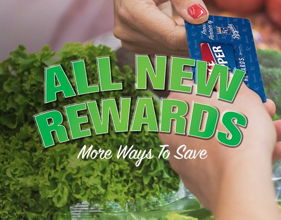 Woman handing cashier a Price Chopper REWARDS card while paying for groceries